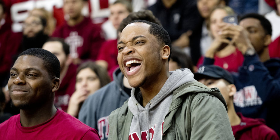 Crowd of students cheering, in foreground male student smiling in Temple sweatshirt
