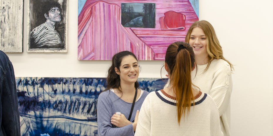 Three students talking at gallery exhibition