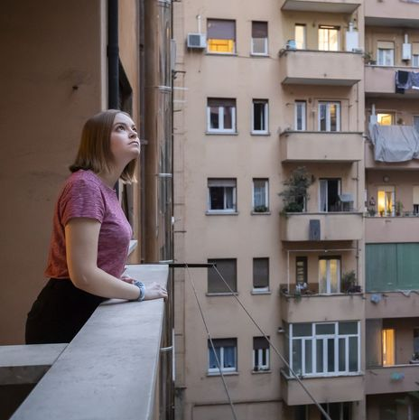 Student looking up from apartment balcony