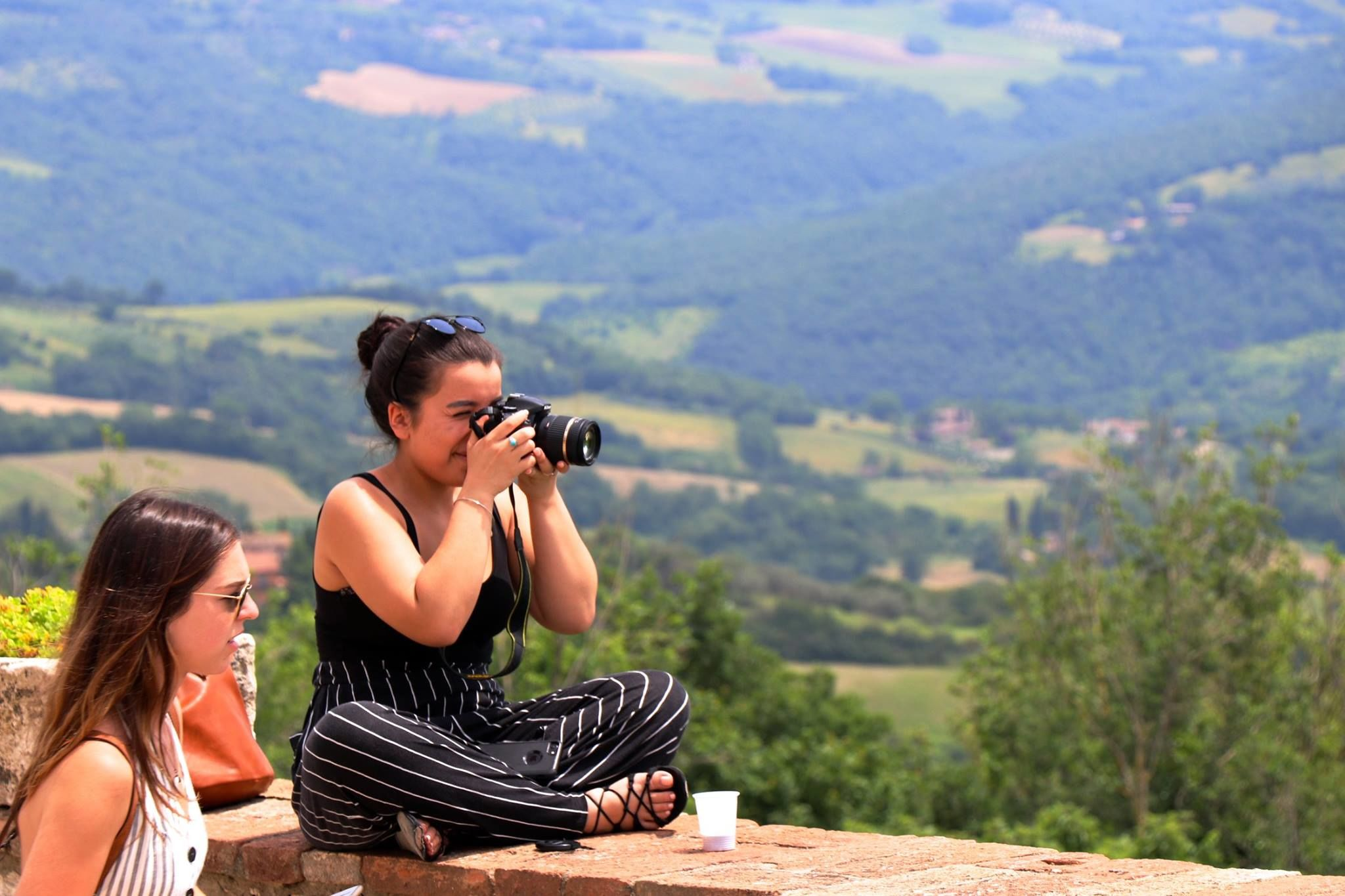 Female student sitting on ledge taking a photo, with another female student to her left. Italian countryside scenery in background.