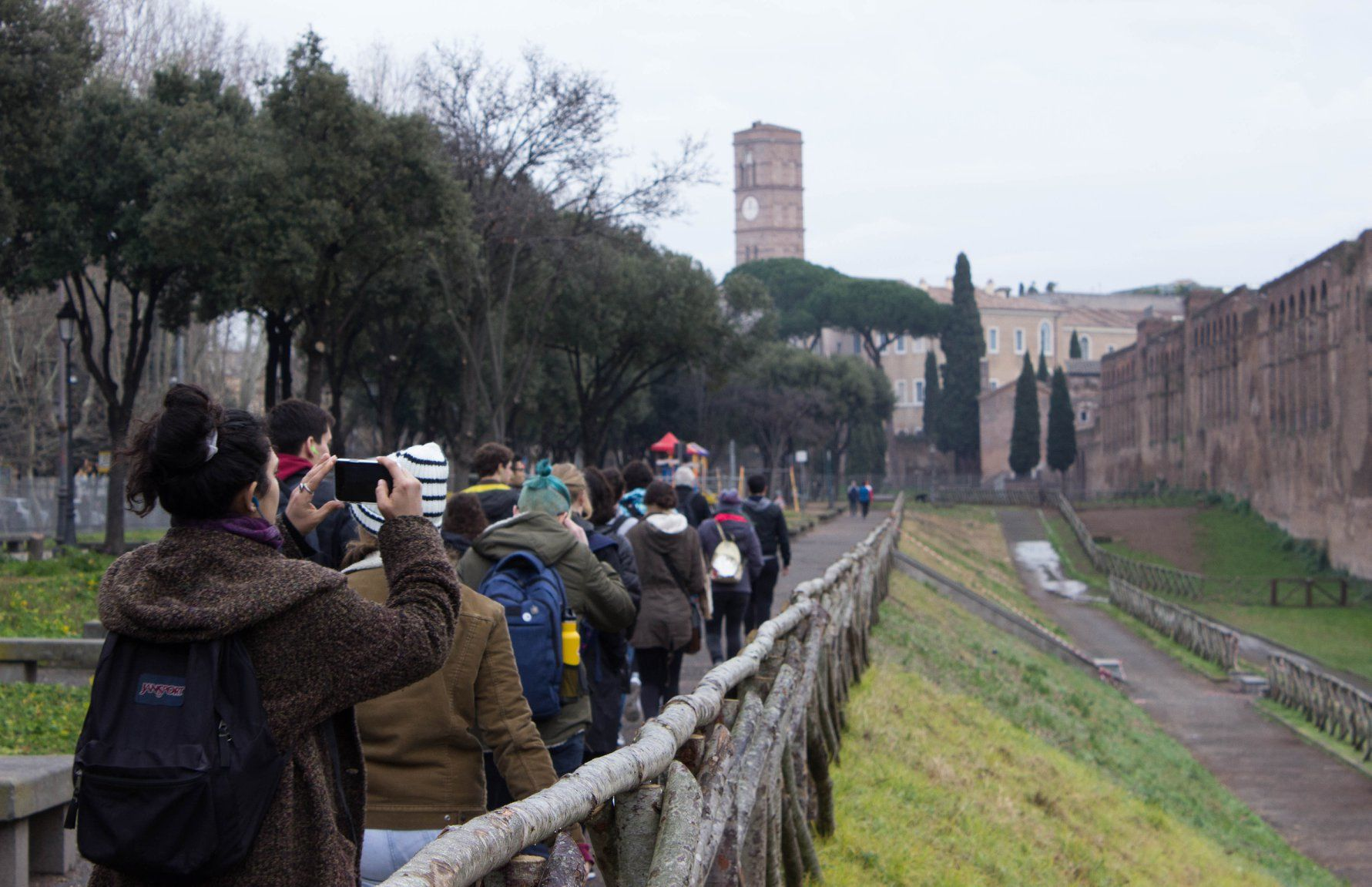 Group of students walking along Aurelian wall of Rome
