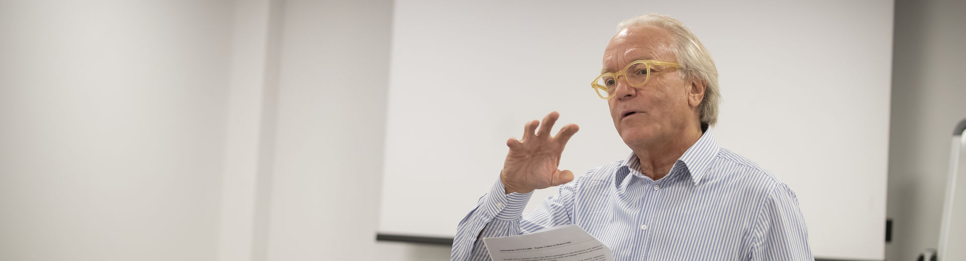 Male professor lecturing to classroom