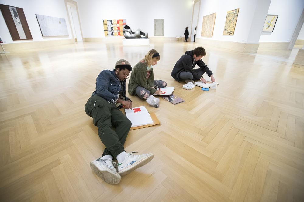 Three students sitting on floor of museum drawing in sketchbooks