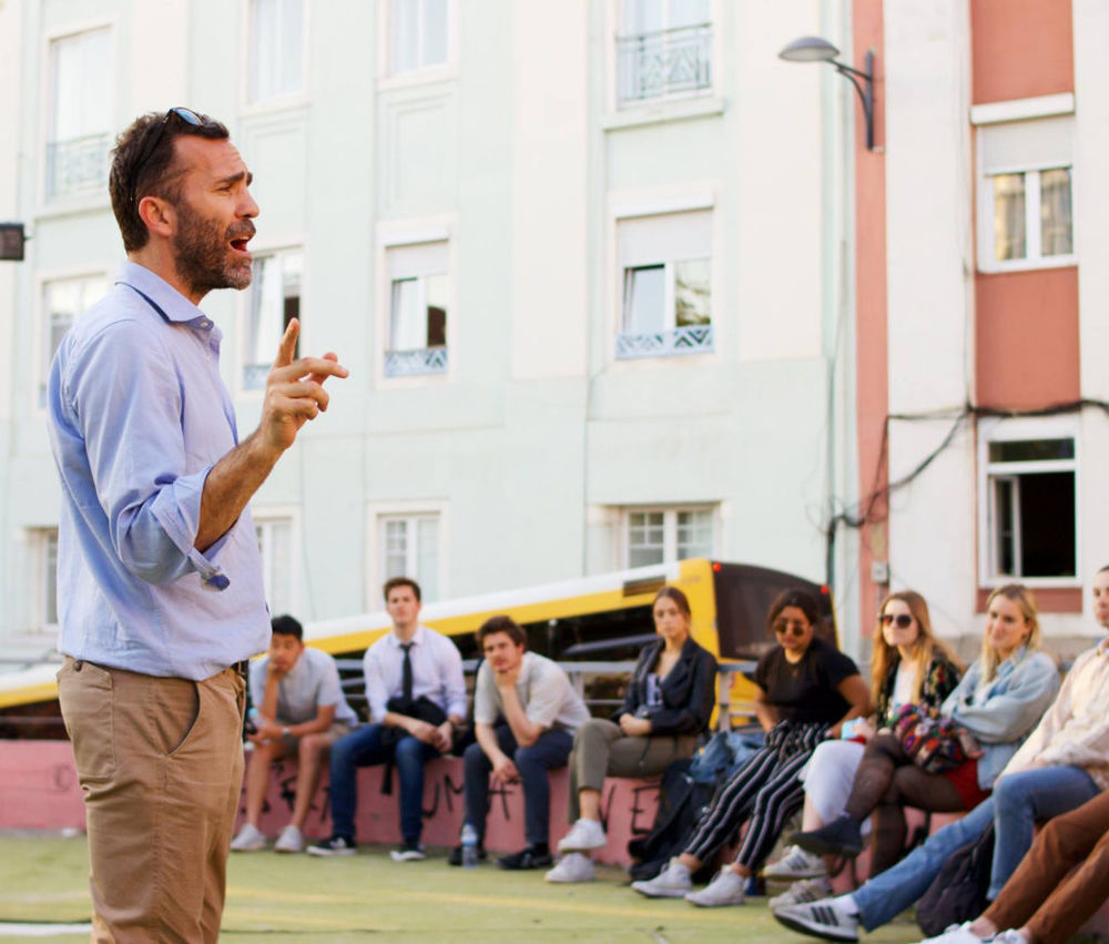 Male professor speaking to students sitting outside in a circle in Portugal