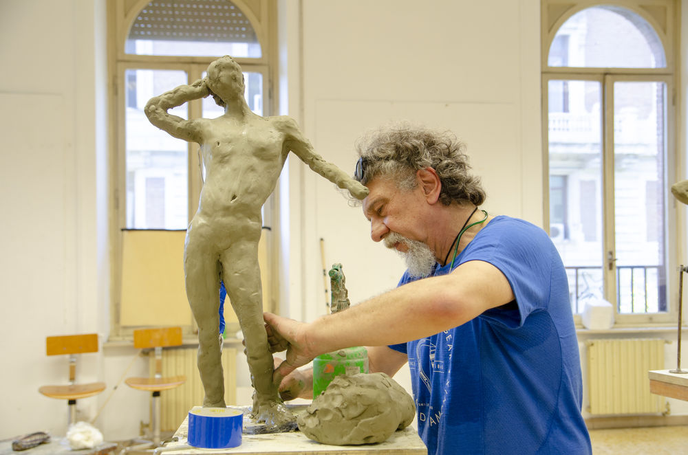 A male adult doing figure sculpting with clay