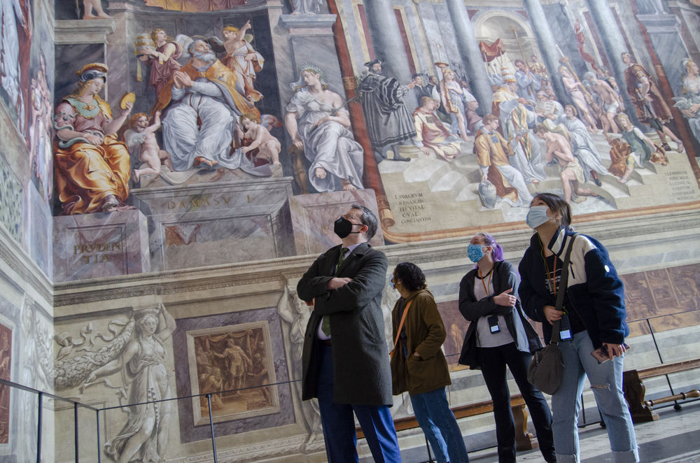 A group of students and their professor looks up at the frescos at the Vatican Museum