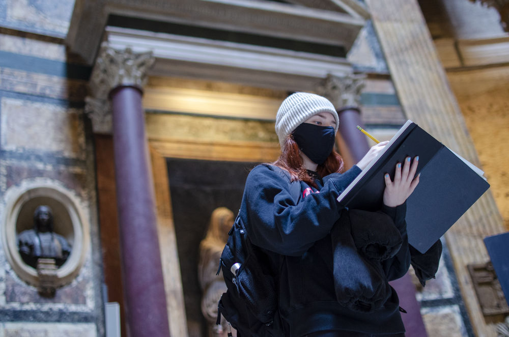 A student drawing in her sketchbook at the pantheon