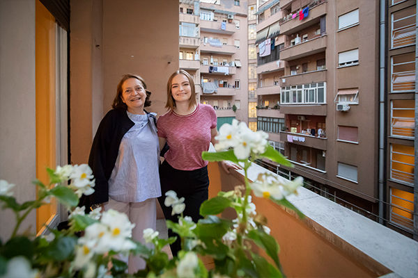 """""""Host mother"""" and female student standing together on balcony"""