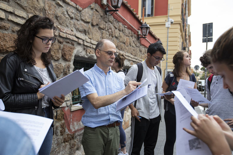 A group of students read worksheets outside in Rome