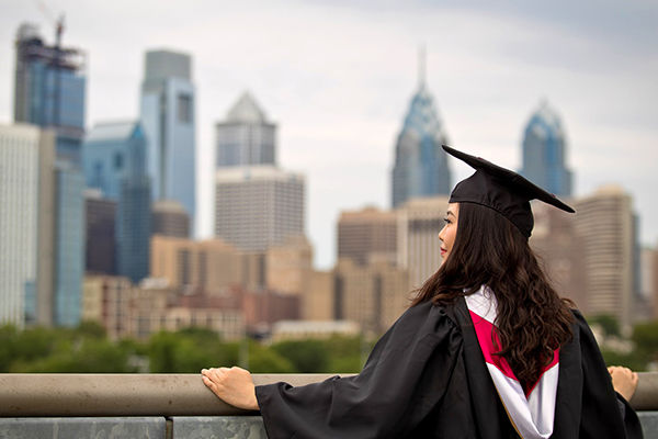 A female student in a graduation cap and gown stands in front of Philadelphia skyline