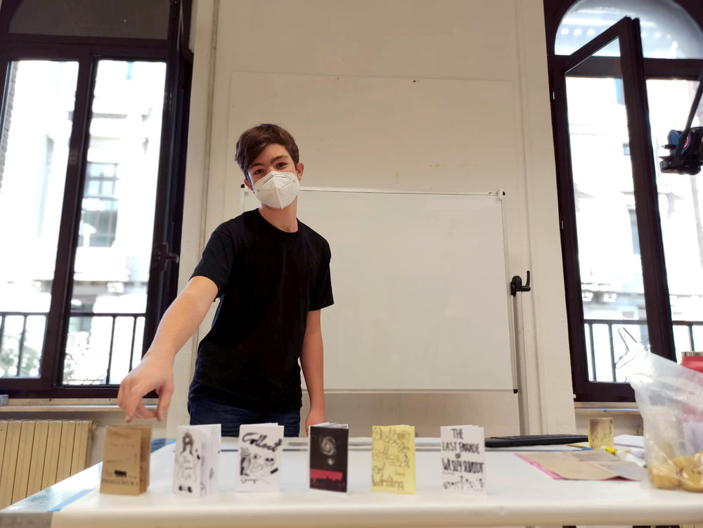 A male student pointing to his handmade zine